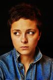 Sad unhappy woman. A beautiful brunette girl with a short cut hair in blue jeans jacket sitting in front of black background and being sad. Her face is showing Royalty Free Stock Images