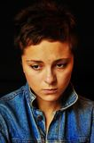 Sad unhappy woman. A beautiful brunette girl with a short cut hair in blue jeans jacket sitting in front of black background and being sad. Her face is showing Royalty Free Stock Photos