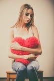 Sad unhappy woman holding red heart pillow Royalty Free Stock Photos