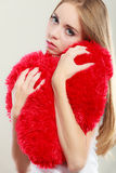 Sad unhappy woman holding red heart pillow Royalty Free Stock Image