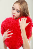 Sad unhappy woman holding red heart pillow Stock Photography