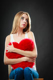 Sad unhappy woman holding red heart pillow Stock Images