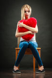 Sad unhappy woman holding red heart pillow Stock Photo