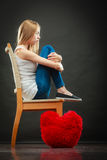 Sad unhappy woman with red heart pillow Stock Photos