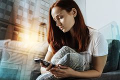 Sad unhappy woman sitting and using smartphone. Useful gadget. Sad unhappy redhead woman sitting in the room on the sofa hugging the pillow and using smartphone stock image