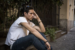 Sad, unhappy young man outdoor, sitting on pavement Royalty Free Stock Images
