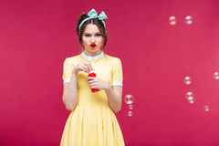 Sad unhappy young woman standing and blowing soap bubbles. Sad unhappy young woman in yellow dress standing and blowing soap bubbles over pink background Stock Photo