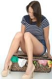 Sad Unhappy Young Woman Wearing Shorts Sitting on an Overflowing Suitcase Stock Image