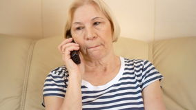 Sad upset good-looking senior woman sitting on sofa at home. Talking with friend via landline. stock video