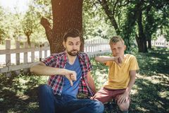 Sad and upset guys are sitting on knees and holding their big thumbs down. Boys are looking on camera with serious sight. They are sitting in park stock image