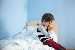 Sad, upset little boy sitting on the edge of his bed. Royalty Free Stock Images