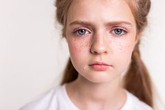 Sad and upset little girl having teardrop on her cheek. Having red freckles. Sad and upset little girl having teardrop on her cheek covered in bright freckles royalty free stock photo