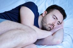 Sad and upset man trying to sleep in bed. Sad and upset man trying to sleep in his bed Stock Images