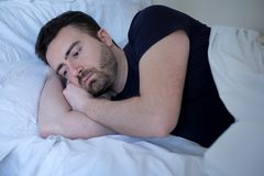 Sad and upset man trying to sleep in bed. Sad and upset man trying to sleep in his bed Royalty Free Stock Photo