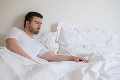 Sad and upset man waking up alone in the morning Stock Image