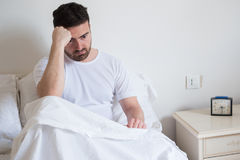 Sad and upset man waking up in the morning. Light Royalty Free Stock Photo