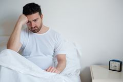 Sad and upset man waking up in the morning Stock Photo