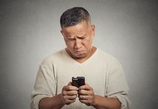 Sad upset middle aged man seeing bad news email text on cellphone Stock Photo