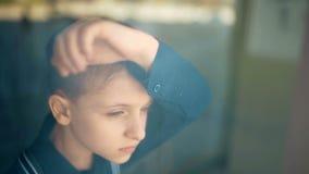 Sad upset tired unhappy kid standing near the window stock footage