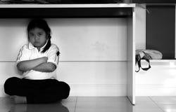 Sad upset unhappy girl kid hiding under the table. stock photos
