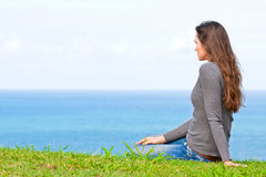 Sad and upset woman sitting by the ocean. A beautiful sad and unhappy young woman sitting in the green grass looking at the ocean stock photos