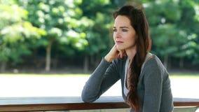 Sad upset woman sitting outdoors. A sad and upset woman sitting down alone outdoors stock video footage