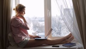 Sad and upset woman using her laptop sitting on window sill. Winter outside the window concept stock footage
