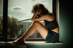 Sad and upset woman in window Royalty Free Stock Image