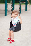 Sad upset worried little small boy toddler in tshirt and jeans shorts on swing on backyard playground Royalty Free Stock Images