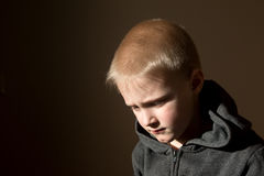 Sad upset worried unhappy little child (boy). Sad upset tired worried unhappy little child (boy) close up horizontal dark portrait with copy space Royalty Free Stock Photo