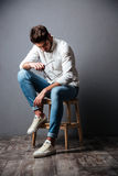 Sad upset young man sitting and looking down Royalty Free Stock Photography