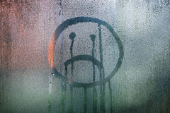 Sad upside down smiley hand drawn symbol. On wet glass background Stock Photography