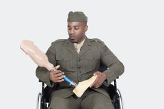 Sad US military officer in wheelchair holding prosthesis foot over gray background stock images