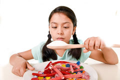 Sad and vulnerable hispanic female child eating dish full of candy and gummies holding sugar spoon in wrong diet concept. Sad and vulnerable hispanic female stock photos