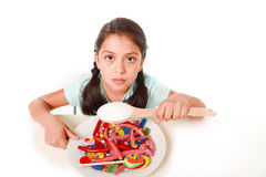 Sad and vulnerable hispanic female child eating dish full of candy and gummies holding sugar spoon in wrong diet concept. Sad and vulnerable hispanic female royalty free stock image