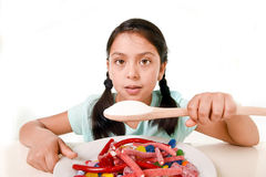 Sad and vulnerable hispanic female child eating dish full of candy and gummies holding sugar spoon in wrong diet concept Royalty Free Stock Photos