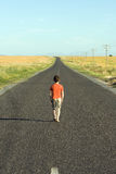 Sad walk. Little boy aged eight, wearing a red shirt, walking down a tarred road, looking sad Royalty Free Stock Photo