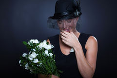 Sad widow crying. Sad widow with mourning clothing and flowers crying at husband's funeral Royalty Free Stock Photography