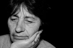 Sad woman. Sad senior woman on black background stock photos