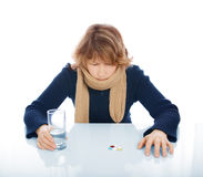 Sad woman. With glass of water and some medicines stock photo