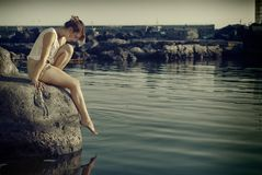 Sad woman. Young sad woman on the rocks royalty free stock photography