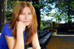 Sad woman. Mature woman looking sad and tired sitting on a park bench Stock Images
