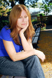 Sad woman. Mature woman looking sad and stressed sitting on a park bench Royalty Free Stock Image