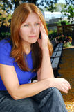 Sad woman. Mature woman looking sad and stressed sitting on a park bench Royalty Free Stock Images