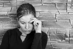 Sad woman. Girl sitting against a brick wall Royalty Free Stock Images