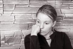 Sad woman. Girl sitting against a brick wall Royalty Free Stock Photography