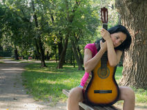 Sad woman with acoustic guitar. In the park Stock Photography