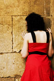 Sad woman against wall Royalty Free Stock Photos
