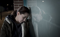 Sad woman alone leaning on street window at night suffering depression crying in pain Stock Images