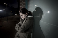 Sad woman alone leaning on street window at night suffering depression crying in pain Royalty Free Stock Photo